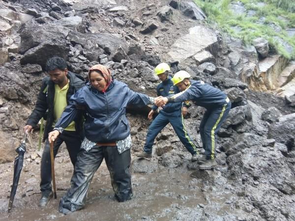 SDRF team helping out a woman pilgrim to cross the muddy track on Kailash Mansarovar Yatra. Photo/ANI