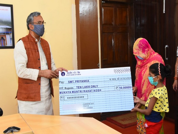 CM Trivendra Singh Rawat handing the cheque to the constable's widow. Photo/ANI