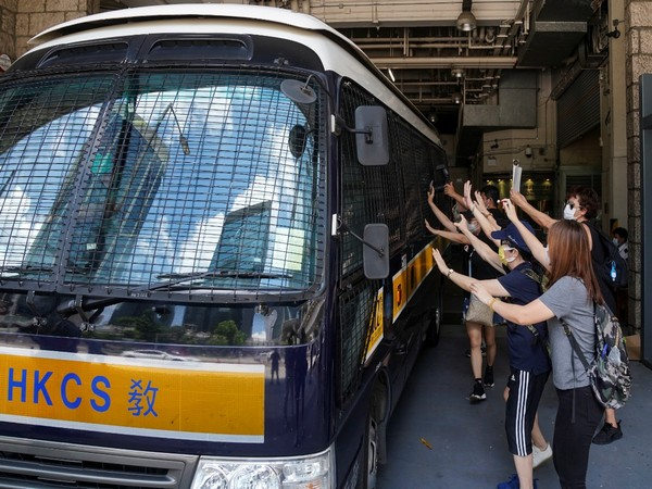 Supporters bid farewell to a prison van transporting Tong Ying-kit,