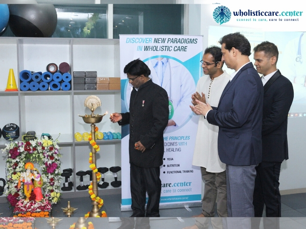 Dr John Ebnezar lighting the auspicious lamp and inaugurating the Wholistic Care Center in Mumbai as Yogi Sakha, Dr Pradeep Singh (centre) and Dr Saurabh Talekar (extreme right) watches.