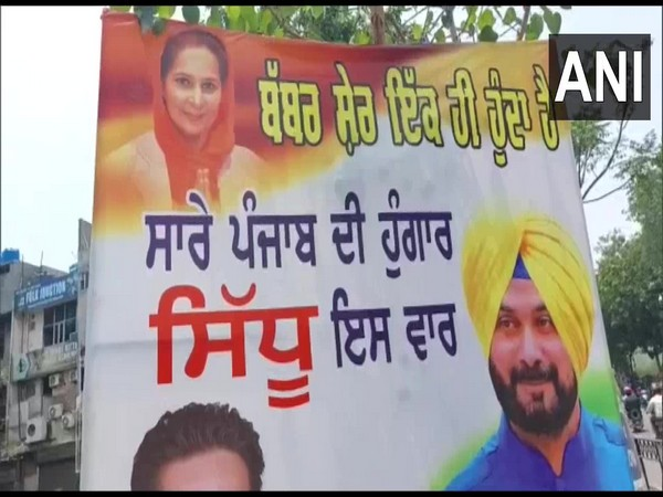 Supporter puts up poster of Congress MLA Navjot Singh Sidhu, his wife in Ludhiana. (Photo/ANI)