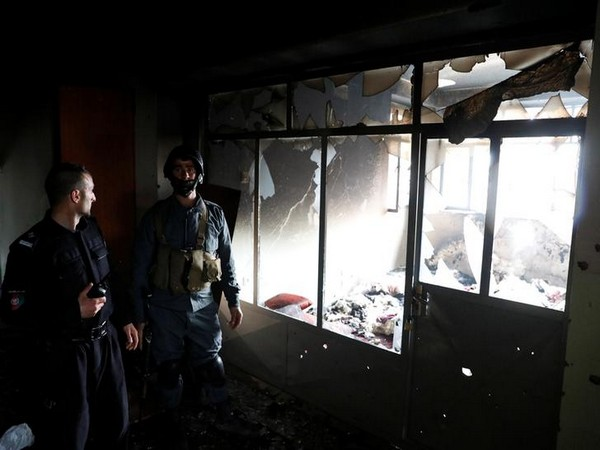 Afghan policemen inspect inside a Sikh religious complex after an attack in Kabul