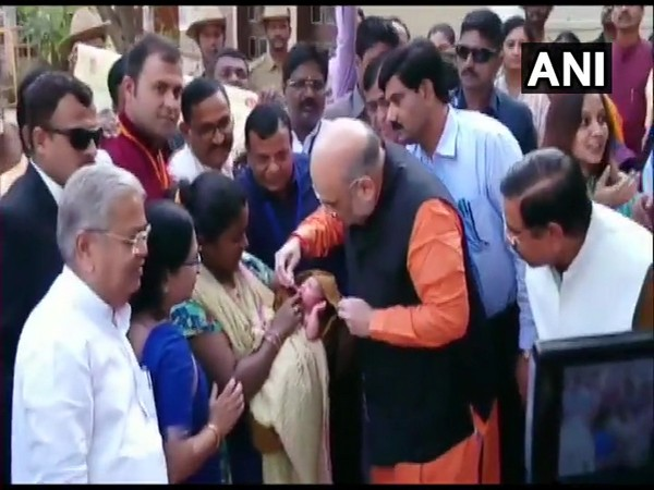 Home Minister Amit Shah administers polio drops to a child on Pulse Polio Day 2020 in Hubballi on Sunday.