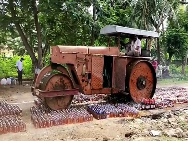 The Krishna district police on Friday destroyed liquor bottles worth approximately Rs 72 lakh, seized in different cases by a road roller. (Photo/ANI)