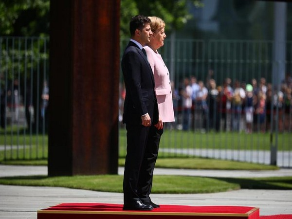German Chancellor Angela Merkel and Ukrainian President Volodymyr Zelensky standing for national anthems outside the chancellery in Berlin on Tuesday.