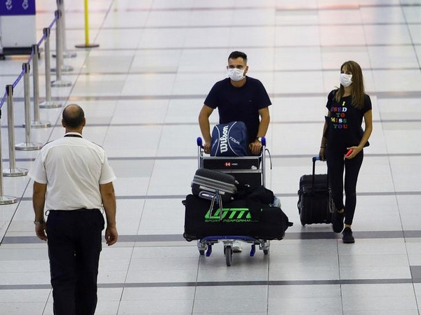 People in face masks walk at Ministro Pistarini International Airport in Buenos Aires