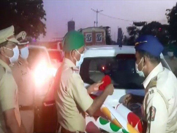 Mumbai Police personnel pasting colour-coded stickers on vehicles of essential services. (Photo/ANI)