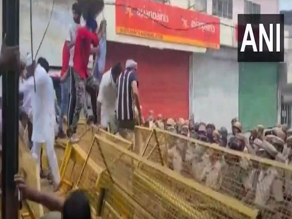 A group of farmers jumping over police barricades (Photo/ANI)