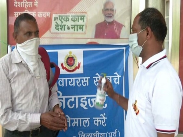 A volunteer providing sanitiser to a man in New Delhi on Tuesday. Photo/ANI
