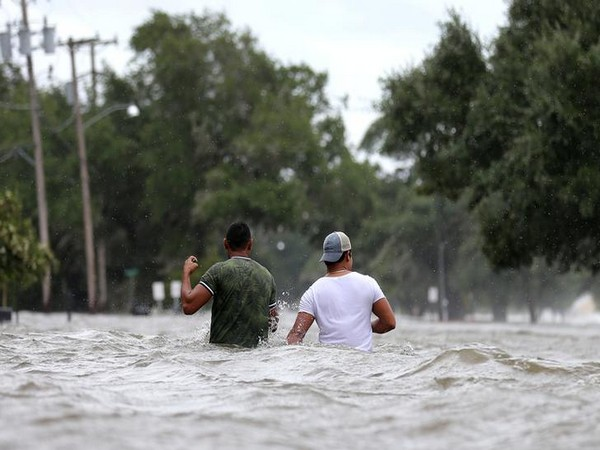 People wade through flood waters caused by Hurricane Barry in Mandeville, Louisiana on July 13 (Photo/Reuters)