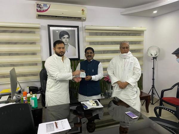 RJD leader Tejashwi Yadav inducting Bihar RLSP president Bhudeo Chaudhury in RJD. (Photo/ANI)