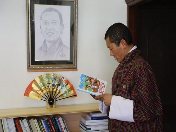 "Bhutanese Prime Minister Lotay Tshering reading PM Modi's book ""Exam Warrior"" (Photo courtesy: PMO BHutan Facebook page)"