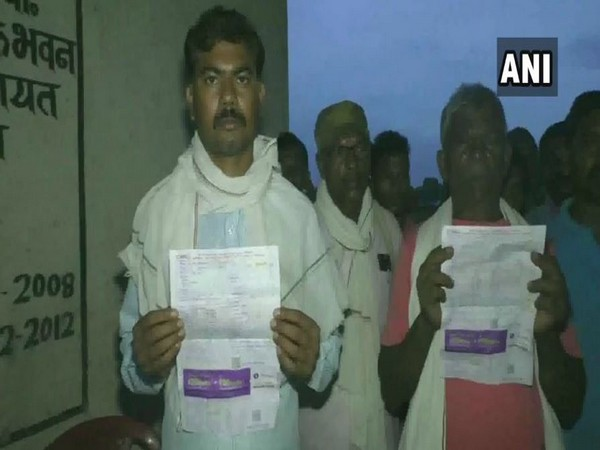 Villagers holding electriciy bills that they reicived without having an electricity supply in Pateri Para of Sanawal village, Chattisgarh. Photo/ANI