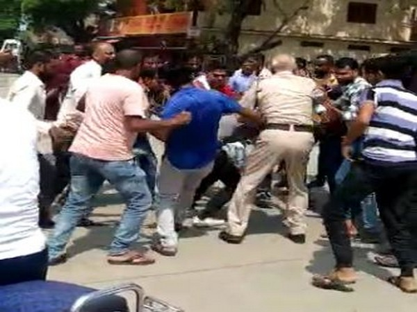 Locals thrashing the accused as the police man intervenes. Photo/ANI