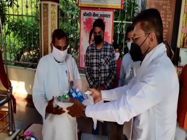 BJP MLA distributing COVID-19 kit (masks, sanitisers, PPE kits) to priests in Kanth village of Moradabad. (Photo/ANI)