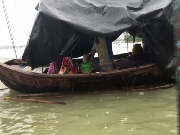 A family has been forced to live in a boat in Prayagraj due to flood. Photo/ANI
