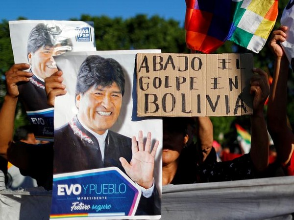 Supporters of Bolivia's ousted President Evo Morales hold a placard that reads 'Down with the coup in Bolivia' outside the US embassy in Buenos Aires, Argentina.
