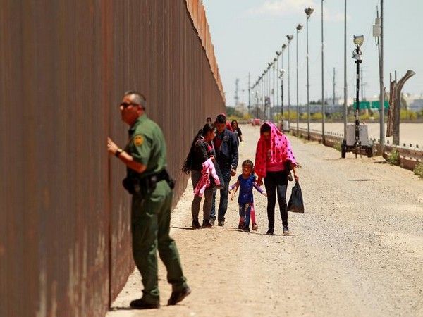 A group of Central American migrants walk next to the US-Mexico border fence after they crossed the borderline while a Border Patrol agent looks through the fence in El Paso, Texas.