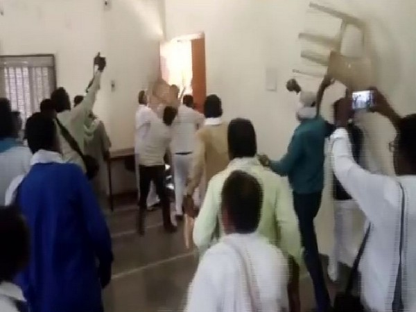Sandeep Tajane escaping from the premises as party workers throw chairs at him. Photo/ANI