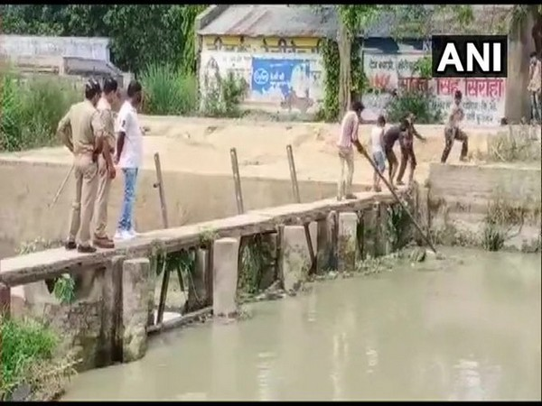 Two policemen in Bulandshahr watch children take out dead body from a canal.