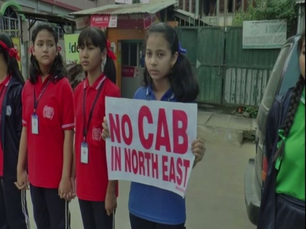 "A girl holding placard ""No CAB in North East"" in a human chain in Imphal on Thursday. Photo/ANI"
