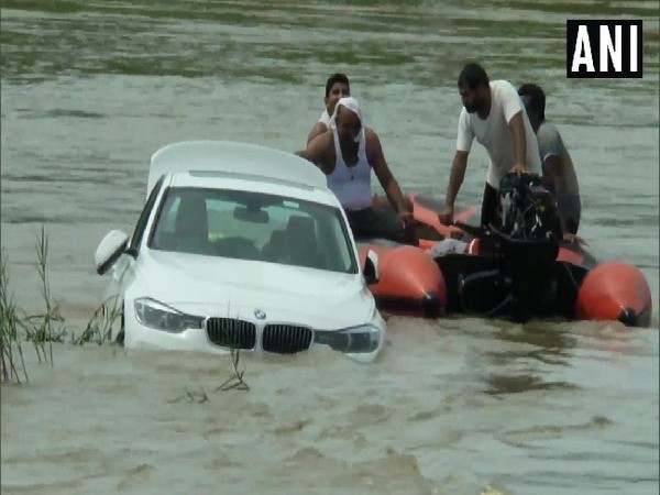 Rescue workers taking out BMW car from a canal in Yamunanagar.