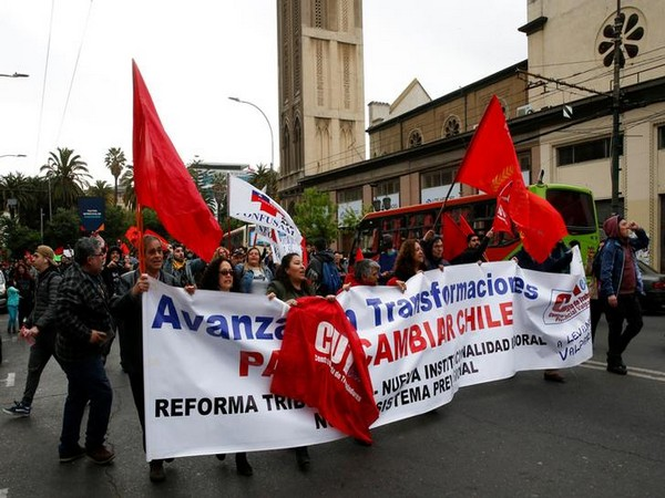 Demonstrators carry banner and flags as they march during a protest against the government in Valparaiso on Saturday