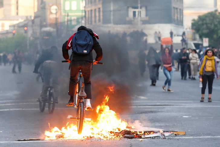 A demonstrator cycles over burning objects on a road during a protest against the government in Valparaiso