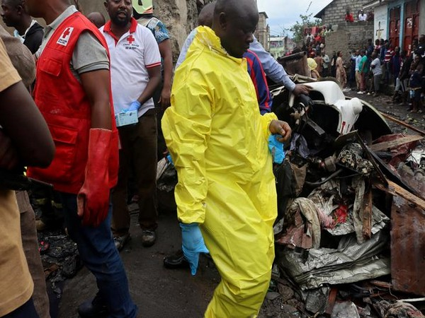 Civilians gather at the site where a Dornier 228-200 plane operated by local company Busy Bee crashed into a densely populated neighbourhood in Goma