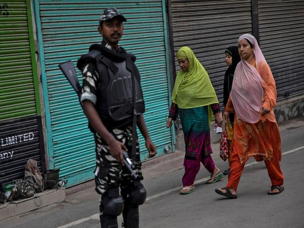 Kashmiri women walk past an Indian security personnel during restrictions in the region