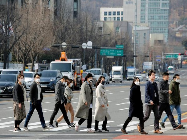 People wearing masks to protect them from coronavirus walk on a pedestrian crossing in downtown Seoul