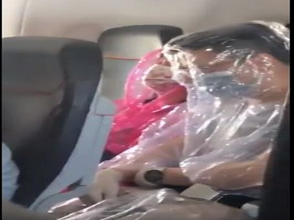 The two passengers were spotted on an unspecified flight covered in sheets of plastic (Picture Courtesy: @Alyss423 Twitter)