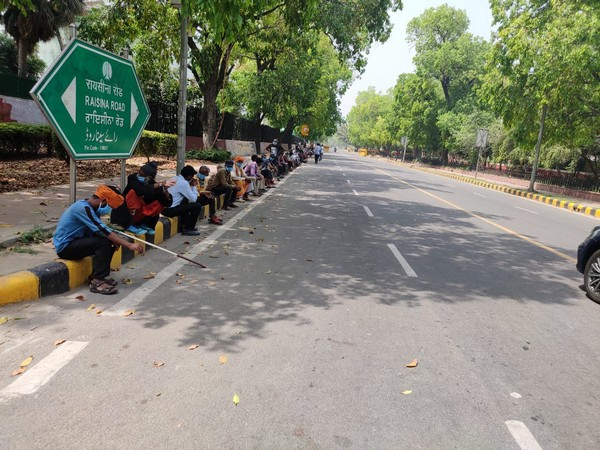 People waiting for the food at Raisina road in New Delhi [Photo/ANI]