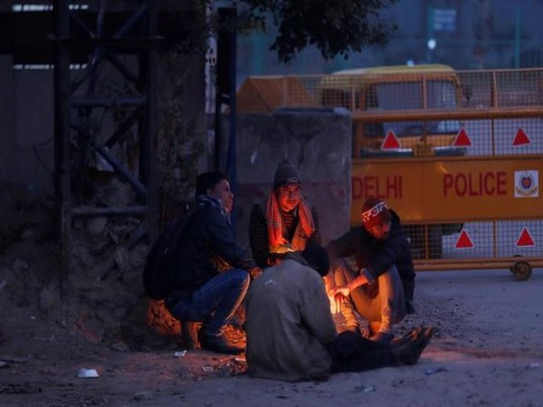 Men sit next to a bonfire on a road side in New Delhi on Saturday. Photo/Reuters