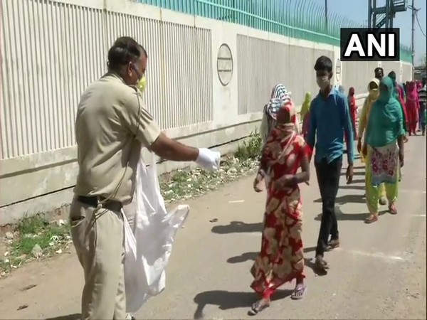 Delhi Police personnel distributing food packets in the national capital on Saturday.