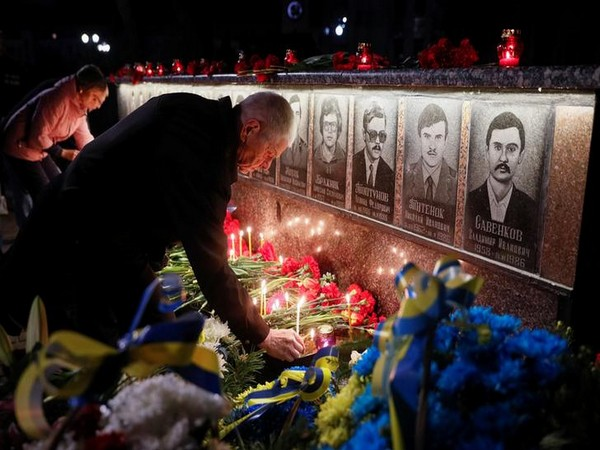 People place candles and flowers at a memorial dedicated to victims of Chernobyl nuclear disaster in Slywchuk in Ukraine
