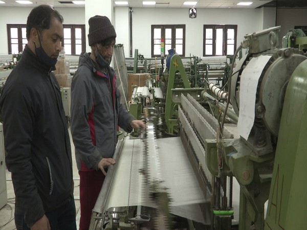 Silk weavers working on new machinery in Srinagar (Photo/ANI)