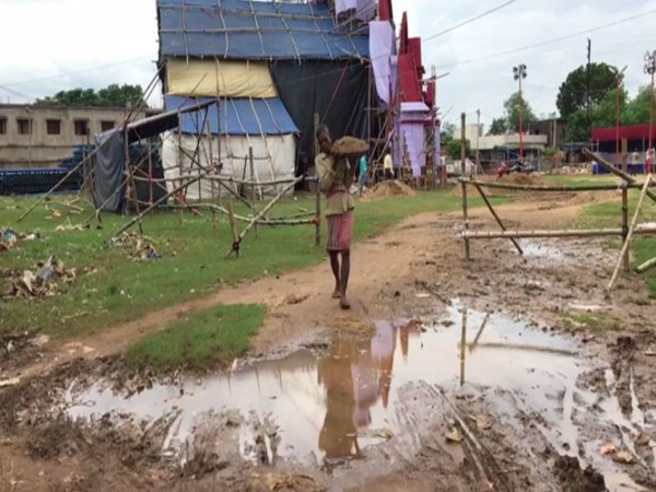 A worker filling soil in the water-logged area of a pandal in West Bengal's Midnapore on Wednesday. Photo/ANI