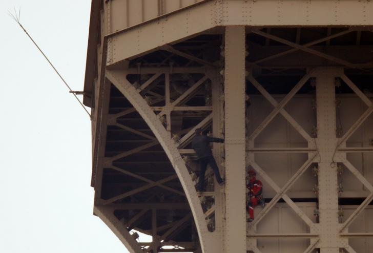 The unidentified man (left) with a rescue worker on the Eiffel Tower on Monday (Photo/Reuters)