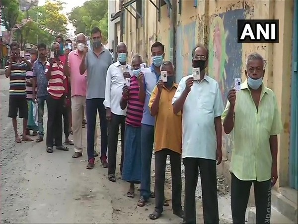 Voters queue up outside a polling booth in West Bengal's Kamarhati. (Photo/ ANI)