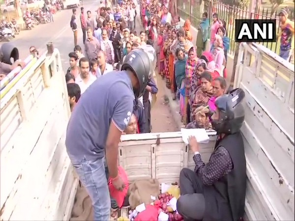 Biscomaun employees selling onions wearing helmets in Patna on Saturday