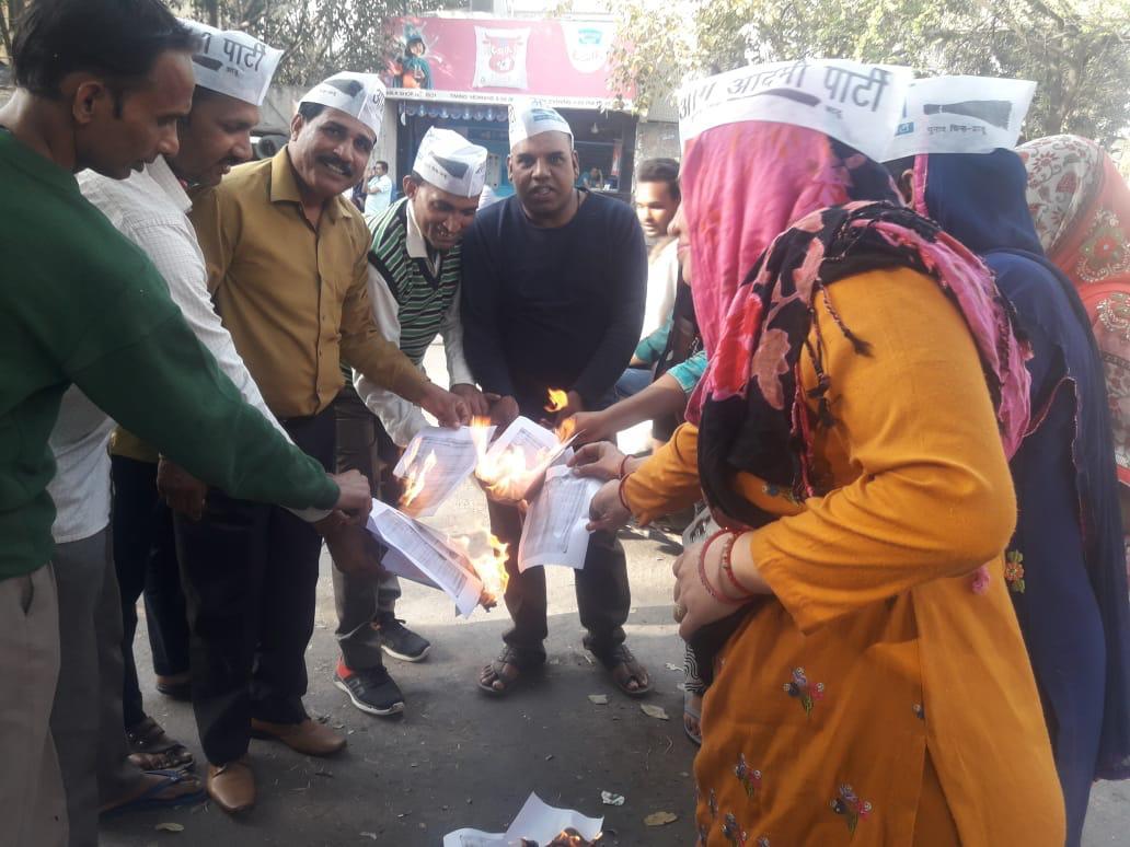 AAP workers burning the copies of BJP's 2014 LS poll manifesto on Sunday. Photo/ANI