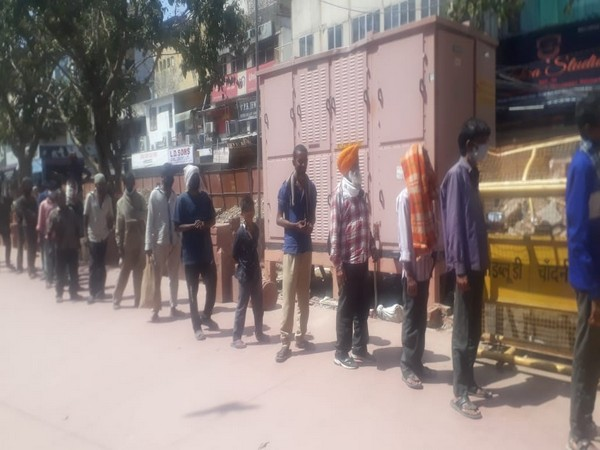 Distribution of food in Chandni Chowk area of the national capital. [Photo/ANI]