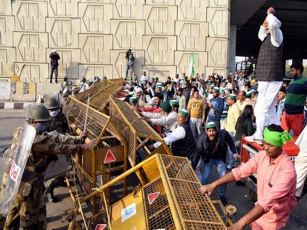 Members of Bhartiya Kisan Union try to remove the barricades as they protest at the Delhi-Gaziabad border, in New Delhi on Sunday. (Photo/ANI)