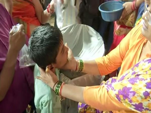 A child taking fish prasadam.