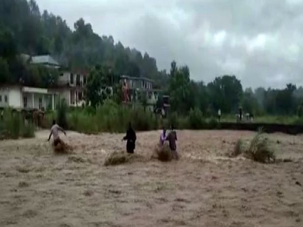 Local resuing three people stranded in the flash flood in a local rivulet in Hamirpur in Himachal Pradesh on Monday. Photo/ANI