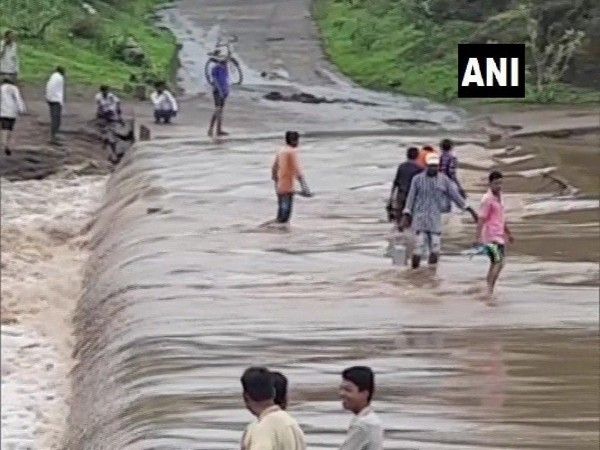 Visuals from a bridge submerged in water due to heavy rain on Sunday in Chhota Udepur. Photo/ANI