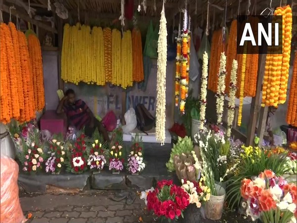 A flower seller awaits customers in Guwahati, Assam. (Photo/ANI)