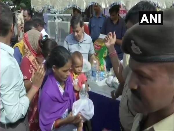 People in long queues to collect flood material distributed by NTPC at Patna on Wednesday