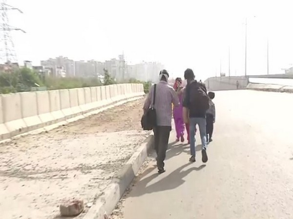 The family of a daily wage earner leaving for their native village at Delhi-Ghazipur border on Thursday. Photo/ANI